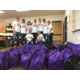 Virginia Tech Alumni alumni stand behind dozens of bags filled with food at the KidsEat! pantry. (Travis Barton/City Journals)