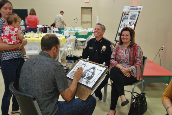 Sandy City Police Chief Kevin Thacker and his wife Gail pose for a caricature artist. (Keyra Kristoffersen/City Journals)