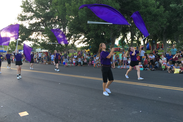 Riverton High School color guard members twirl flags during the 2016 Town Days Parade. (Tori La Rue/City Journals)