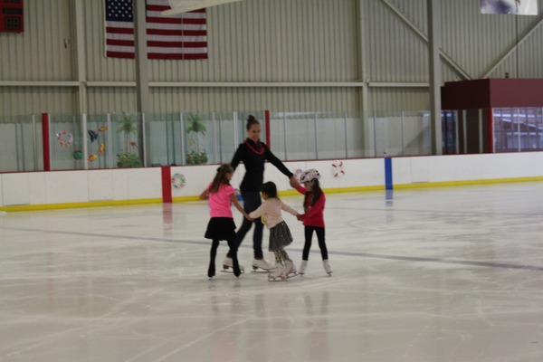 Students form ring around Caitlin Ross during summer Learn to Skate Ice Show.