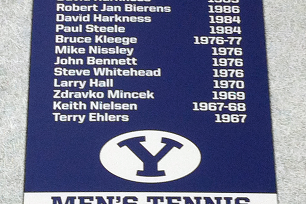 A photo of a flag with a list of BYU's All-American tennis players that hangs above BYU indoor tennis courts. (Debbie Bennett)