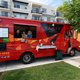 Spencer Herrera with husband Dallas Olson and friend Maizee Thompson show off their bright red Facil Taqueria truck. (Keyra Kristoffersen/City Journals)