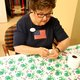 Charlene Jenson ties a baby quilt that will eventually be donated. (Keyra Kristoffersen/City Journals)