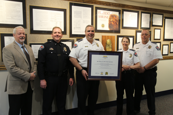Former West Valley City Police Chief Lee Russo (center) holds the CALEA accreditation certificate after the police department was awarded the distinction in May. (Kevin Conde/West Valley City)
