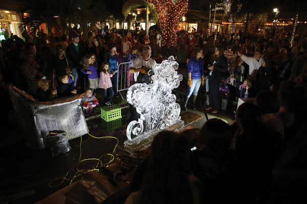 An ice sculpture draws a crowd on Third Street South.