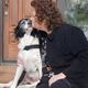 Executive Director of Crisis Center North, Grace Coleman, receives a kiss from Canine Advocate Penny before a speaking