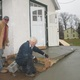 Minister Chuck Wyeth left and Larry Steiner work on the freshly poured concrete access ramp at the Kelton Church of Christ