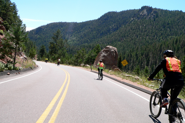 The Pikes Peak Bike Tours support van follows riders down the mountain, carrying water and supplies. Riders wear high-visibility vests because they share the highway with visitors in cars. Photo courtesy of Nathan Scott of Bike Pikes Peak Tours.