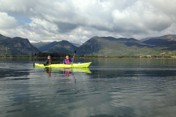 Kayakers paddle on the freshwater reservoir known as Lake Dillon, nestled among the mountains. Photo by Alison Roberts-Tse.
