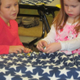 Two girls help make a fleece quilt at Unionville Elementary.