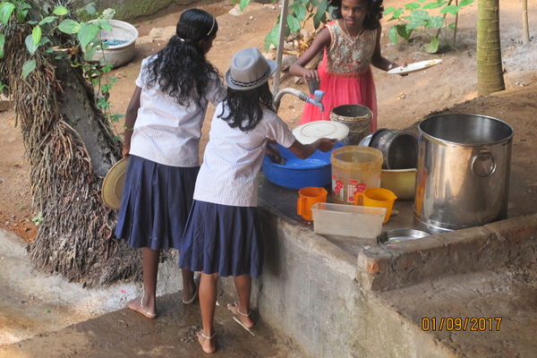 Girls, dressed in their school uniforms, wash breakfast dishes. Everyone gets up early to do chores, study and prepare for the day ahead.