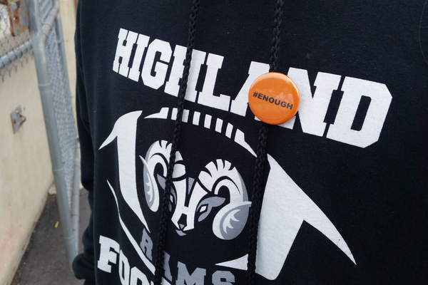 "Orange buttons with the hashtag ""enough"" were handed out at Highland High School on March 14 as part of the national walkout. (Lori Gillespie/City Journals)"