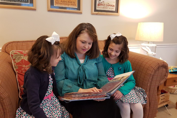 Former Ridgecrest Elementary student and choir member Elizabeth Jensen shows her daughters her Philo T. Farnsworth scrapbook. (Curt R. Jensen)