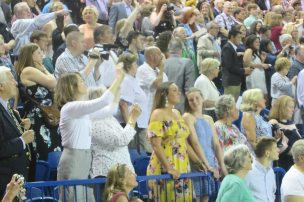 Family members wave and take photos from the stands.
