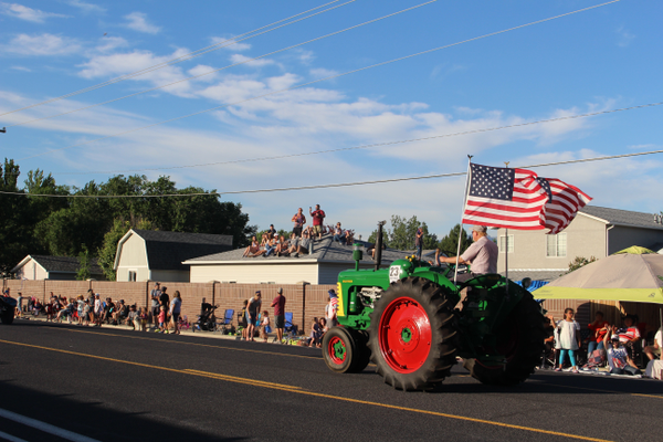 Parade watchers climbed atop a roof to watch the parade, which included this tractor with the American flag. (Travis Barton/City Journals)