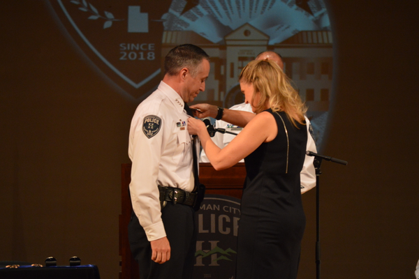Chief Troy Carr has his badge pinned on by his wife. (Justin Adams/City Journals)