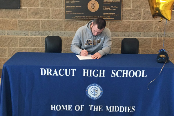 Dracut High senior Allyn French, accompanied by his family, signs his letter of intent to play lacrosse for Merrimack College next fall. (DHS Athletic Dept. photo)