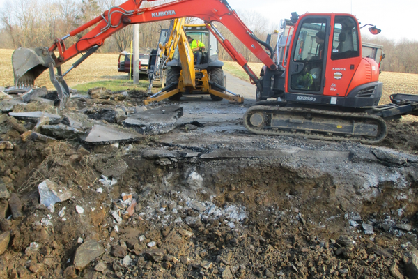 A backhoe clears pavement after the old bridge was removed.