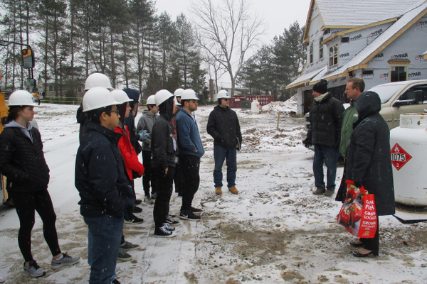 Students gather at the Stonehouse construction site before beginning their tour.