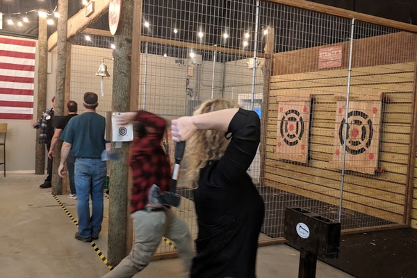 Patrons take turns aiming hatchets at wooden targets.