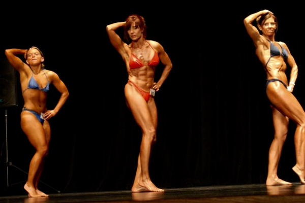 Katie Davis (left) participating in a bodybuilding competition.