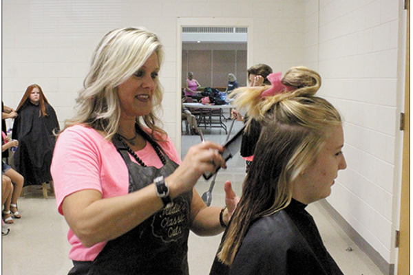 Stylist Trudie Homesley, of Trudie's Classic Cuts, downtown Cherryville on Main Street, talks with 12-year-old Katherine Fenstermacher, as she cuts her hair. (photos by MEP/The Eagle)