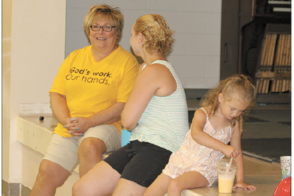 One Body, One Mission co-chairperson Kim Eaker (in yellow tee-shirt) talking with a friend about the One Body, One Mission Community Back Pack School Supplies Drive event, now in its seventh year.