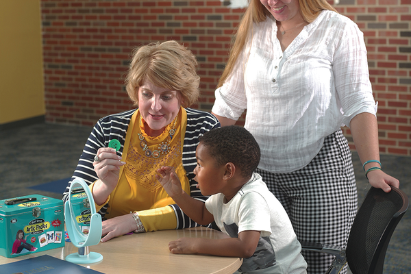 Mary Beth Mason, Ph.D. and student Quinn Ursprung '20 work with a child on speech-language techniques.