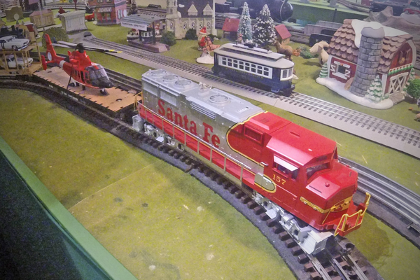 The O-gauge Santa Fe locomotive pulls its cargo around the track.