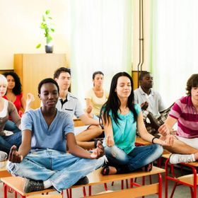 Group of teenagers sitting on the desk in lotus position picture id143917488