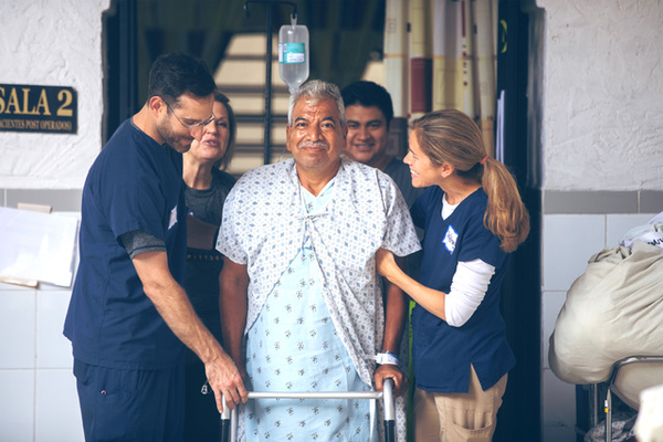 Operation Walk Pittsburgh team members accompany a patient out of the hospital as he makes his journey home after surgery.
