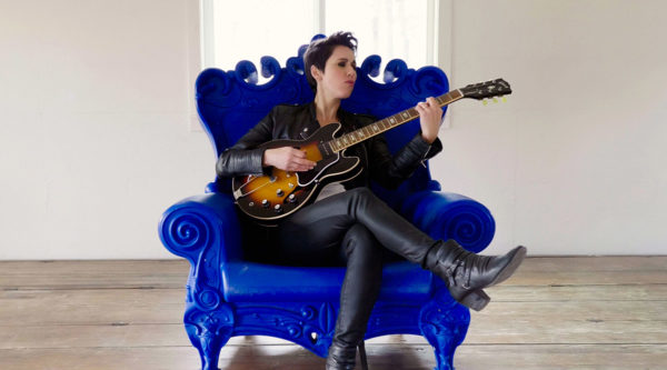 Gina Chavez, blue chair, with guitar
