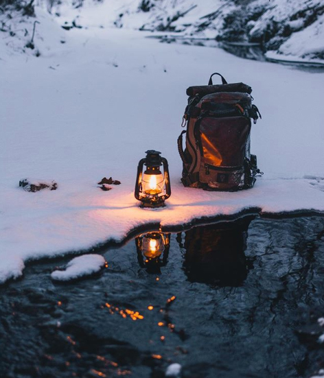 backpack/lantern in snow, water's edge