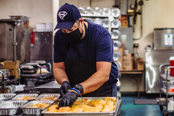 man prepping meals in industrial kitchen