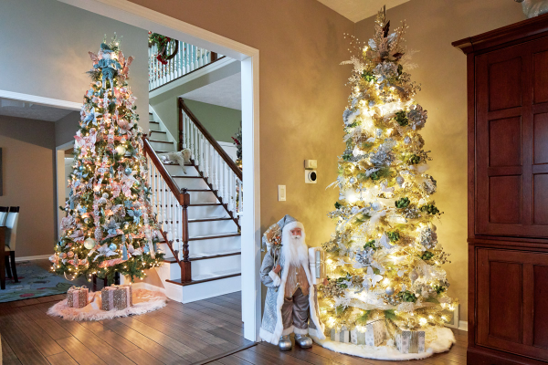 two Christmas trees in foyer, staircase
