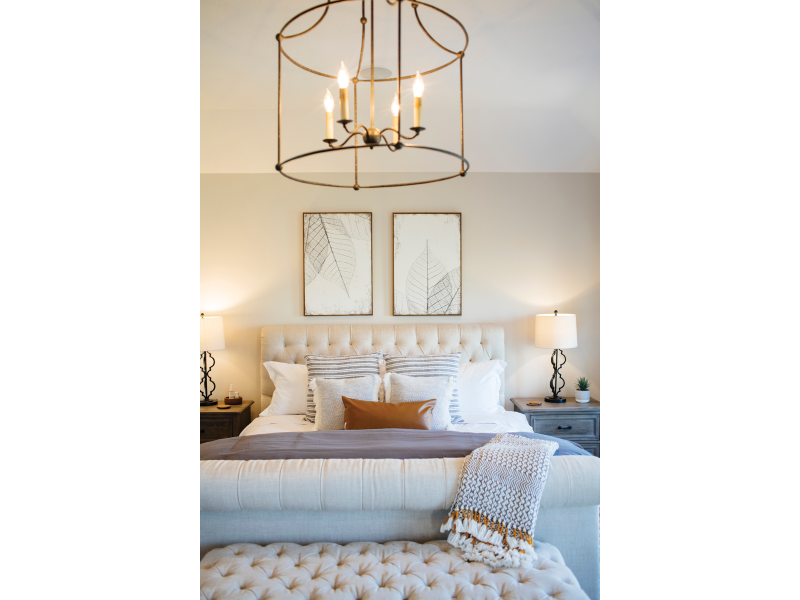 white padded bed, brass chandelier
