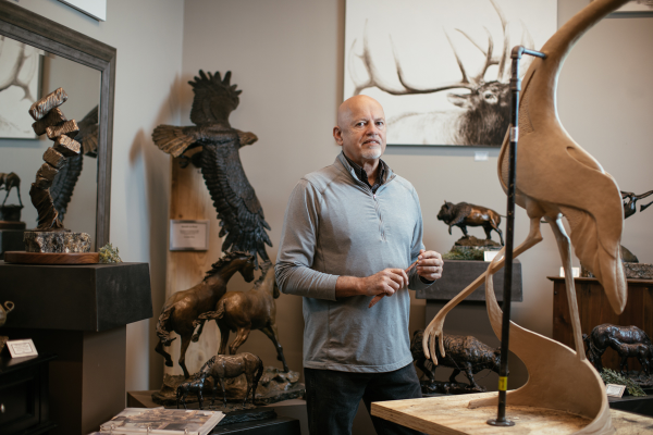 Dave Biehl poses amid several animal statues
