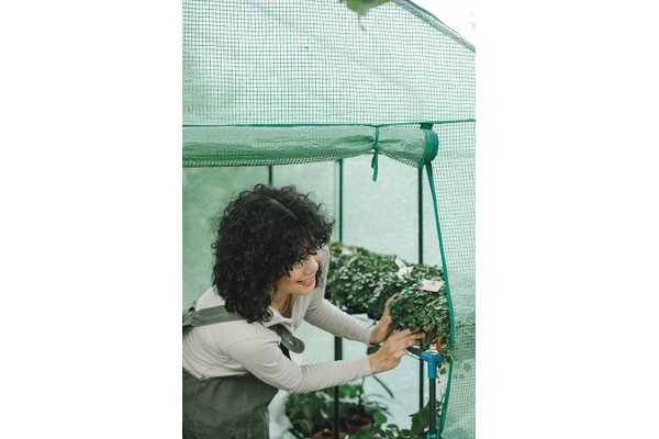 A woman tending to her plants in a small greenhouse