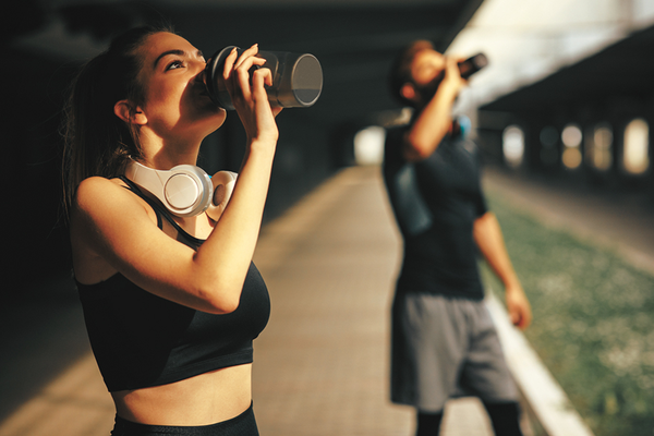 Eco-friendly athletes drinking from sustainable, green water bottles after working out