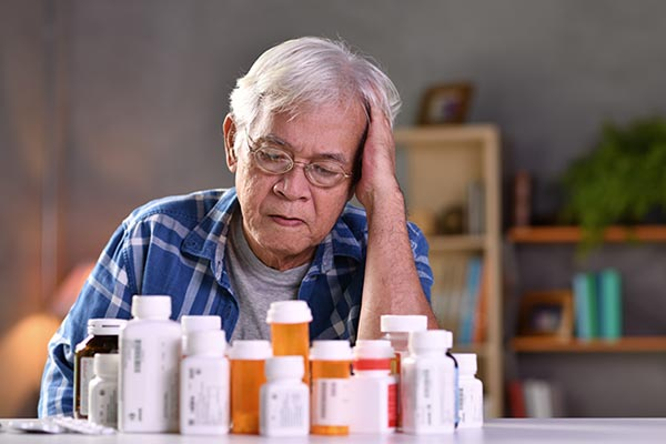 Elderly man stares down confused at dozen or so bottles of pills on table in front of him.