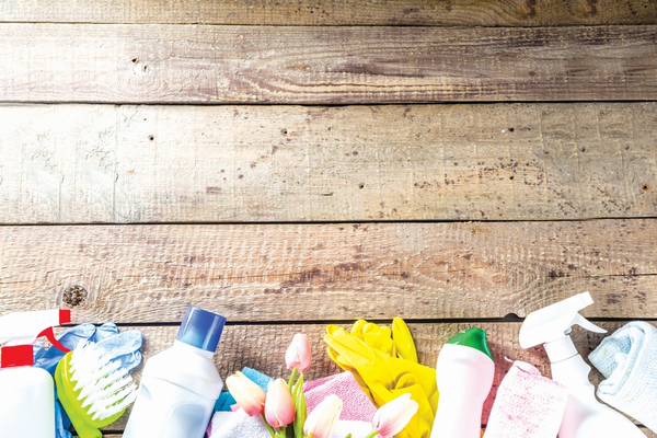 Several bottles of cleaning products along with cleaning brushes on wood planks