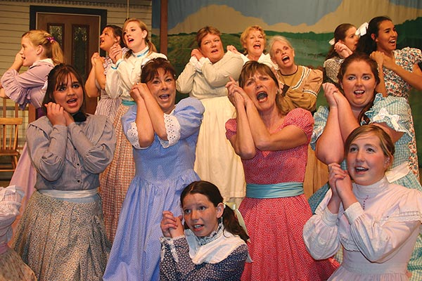 "Group of 14 ladies in costume pose while performing in ""Oklahoma!"" for Magic Circle Players"