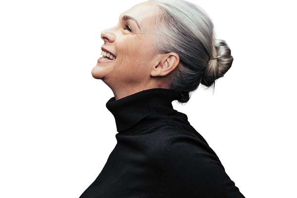 Happy, healthy, satisfied woman with her hair pulled back wearing a black turtleneck sweater smiling looking up