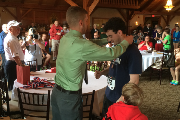 Nick Pearson presents a medal to 20-29 men's age group winner Dominic Mangano at the Tewksbury Memorial Day 5K Fun Run.