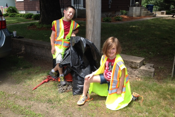 Tyler Barnes and Lydia Barnes help their mom Cheryl clean up in the Pleasant Street area on Saturday.