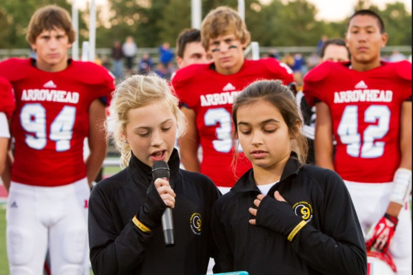 Annie and friend Olivia Panos speak about G9 at an Arrowhead High School football game